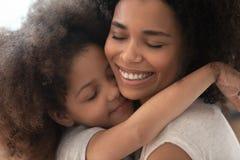 Omfamning för dotter för lycklig tillgiven afrikansk familjmamma och för litet barn royaltyfria bilder