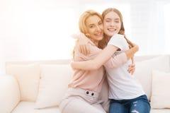 Omfamning för mamma och för tonårs- dotter arkivfoto
