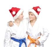 Omfamning för två pojkar i en kimono och en bärande jultomtenhatt Arkivfoto