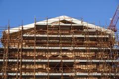 Omfattande material till byggnadsställning som ger plattformar för pågående arbete på en kyrka i omstrukturering Fotografering för Bildbyråer