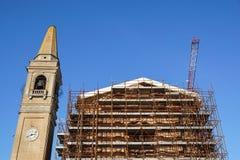 Omfattande material till byggnadsställning som ger plattformar för pågående arbete på en kyrka i omstrukturering Arkivbilder
