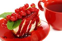 Omfloers cake en een rode kop thee. Stock Afbeeldingen