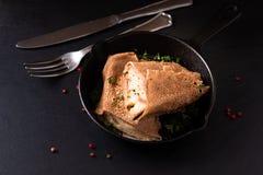 Omfloersen de de eigengemaakte Ham en Kaas van het voedselconcept dat in ijzerkoekepan op zwarte leiachtergrond wordt gegoten stock afbeelding