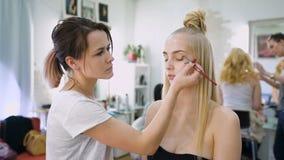 omformning I den moderiktiga skönhetsalongen förbereder en yrkesmässig makeupkonstnär bilden för en attraktiv blondin stock video