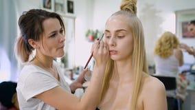 omformning I den moderiktiga skönhetsalongen förbereder en yrkesmässig makeupkonstnär bilden för en attraktiv blondin lager videofilmer