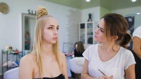 omformning I den moderiktiga skönhetsalongen förbereder en yrkesmässig makeupkonstnär bilden för en attraktiv blondin arkivfilmer