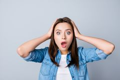 Omg! Close up portrait of amazed girl with wide open mouth and e. Yes in casual wear, holding head with her hands, wondering what happened, looking confused stock photos