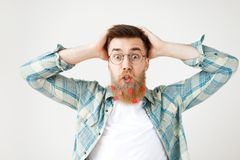 Omg concept. Bearded fashionable male expresses big shock, stares at camera, wears checkered shirt and round spectacles royalty free stock images