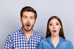 Omg! Noway! Curious shocked couple, standing in casual shirts, i. Solated on pure background with wonderment Royalty Free Stock Photos