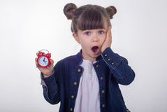 Omg, sveglia! Ragazza sorpresa in vestito con l'orologio rosso su fondo bianco Sveglia colpita della tenuta del bambino immagine stock libera da diritti