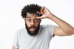Omg unbelievable. Portrait of impressed and surprised handsome adult african american bearded guy taking off glasses stock photos