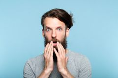 Omg shocked astounded man open mouth emotion. Omg unbelievable shock amazement. astounded man with open mouth. portrait of a young bearded guy on blue background stock images