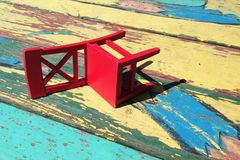 Omgedraaide rode stoel op een kleurrijke achtergrond stock afbeeldingen