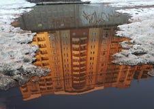 Omgekeerde diagonale bezinning van een oranje gebouw in grijze vulklei, langs de randen van gebroken stukken van witte sneeuw Stock Foto