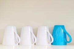 Omgekeerde koffie en theemokken met één die duidelijk uitkomen Stock Foto