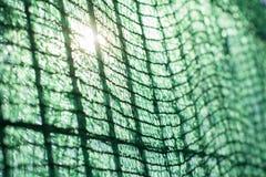 Omheining in een groene tarp met de zonstralen wordt behandeld die doorkomen die Stock Foto's