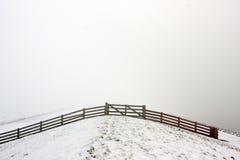 Omheining op een nevelige, sneeuwdijk Stock Fotografie