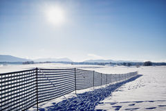 Omheining tegen sneeuwbank Stock Afbeeldingen