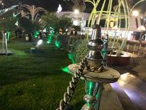 Omheining van de metaal de mooie omheining met kettingen in een nacht feestelijke stad, in een park op een achtergrond van gras i stock fotografie