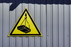 Omheiningsachtergrond met waarschuwingsbord over gevaar van dalende lading van kraan stock afbeelding