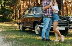 omhels De liefde en de affectie tussen jongelui koppelen bij het park, dichtbij de oude auto een kerel in een plaidvliegtuig en j royalty-vrije stock foto's