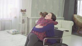 Omhels een gehandicapte moeder in een rolstoel en haar tienerdochtermeisjes stock videobeelden