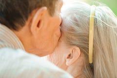 Omhels en kus van oud paar in een park op een zonnige dag royalty-vrije stock foto