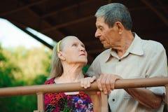 Omhels en kus van oud paar in een park op een zonnige dag stock foto's