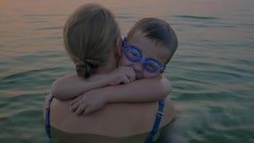 Omhelzingen en kussen van moeder met zoon in het overzees stock videobeelden
