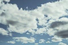 Omhoog bekijkend een blauwe donkere de zomerhemel met pluizige, zachte witte wolken - Concept dagdromen, weer of meteorologie royalty-vrije stock foto's
