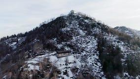 Omhoog beweegt boven pijnboomhout bos en sneeuwberg in de herfst of de winter bij zonsondergang De bouw of kerk over de bovenkant stock videobeelden