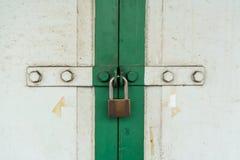 Omhoog gesloten op uitstekende witte en groene houten deur met zilveren slot stock foto