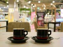 Omhoog gesloten twee koppen van hete koffie op de lijst van de koffiewinkel ` s Royalty-vrije Stock Afbeeldingen