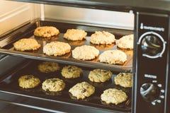 Omhoog gesloten van hete de rozijnenkoekjes van het bakselhavermeel op zwarte plaatpan in de oven, die rozijn en haver voor hoofd royalty-vrije stock afbeelding