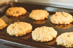 Omhoog gesloten van hete de rozijnenkoekjes van het bakselhavermeel op zwarte plaatpan in de oven, die rozijn en haver voor hoofd stock fotografie