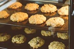 Omhoog gesloten van hete de rozijnenkoekjes van het bakselhavermeel op zwarte plaatpan in de oven, die rozijn en haver voor hoofd stock foto