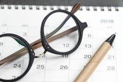 Omhoog gesloten van oogglazen en pen op kalender die als datum gebruiken orgain Royalty-vrije Stock Foto's