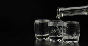 Omhoog het gieten van schoten van wodka van een fles in glas tegen zwarte achtergrond royalty-vrije stock foto's
