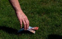 Omhoog het met de hand plukken van geld van de grond Zwitserse munt grasgrond royalty-vrije stock afbeeldingen
