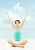 Omhoog opgeheven vrouwenhanden Het zitten in yogalotusbloem stelt over hemel backg Stock Fotografie
