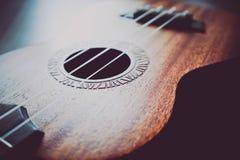 Omhoog sluit de macromening van de ukelelegitaar, koorden De foto schildert muziek af Stock Foto