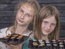 Omhoog sluit het jonge meisje van het portretpaar met sushi, Stock Afbeelding