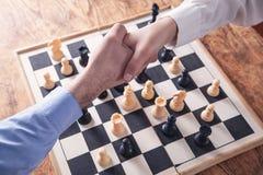 Επιχειρηματίες που τινάζουν τα χέρια Παίζοντας παιχνίδι σκακιού στοκ φωτογραφία