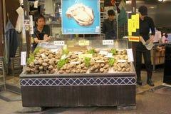 Omicho-Lebensmittel-Markthalle Austern des Mannmarktverkäufers frische, Kanazawa, Japan Stockbilder