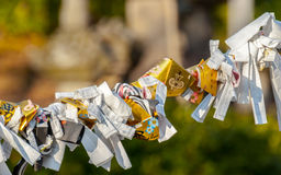 Omikuji tied to a wire. Omikuji or random fortunes tied to wires in temple grounds Royalty Free Stock Images