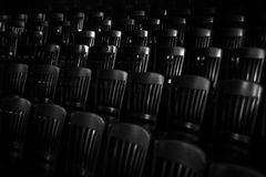Ominous chairs. Chairs seem to stand in judgment in the darkness stock photography