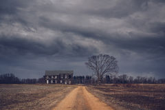 Ominous clouds over an abandoned farm house. A dirt road leads up to an abandoned home and eerie tree on a cloudy day stock image