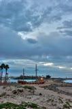 Ominous clouds over California beach park. Ventura Marina Park lights shining under threatening clouds stock image