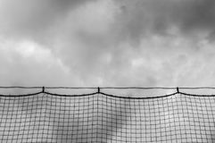 Ominous clouds viewed through baseball netting. Ominous black clouds viewed through a baseball field backstop netting Stock Photo