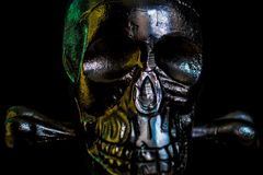 Metal skull on black background. Ominous glare on a metallic skull in the dark stock photography